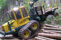 : A forwarder with eight wheels and bogie tracks is driving backwards from a skid trail on a fairly steep slope towards a forest road.